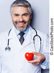 Confident cardiologist. Confident mature doctor holding heart shape toy and smiling while standing against grey background