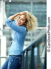 Confident carefree woman with hand in hair