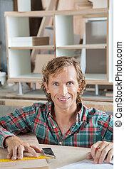 Confident Carpenter Smiling At Workbench
