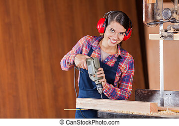 Confident Carpenter Using Drill Machine In Workshop