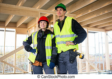 Confident Carpenters In Reflective Jackets At Construction Site