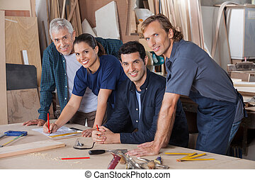 Confident Carpenters Working At Table In Workshop