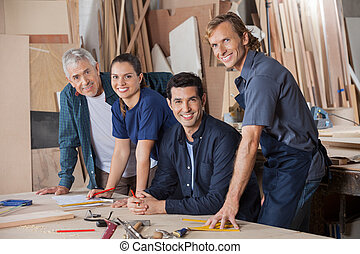 Confident Carpenters Working At Workshop Table