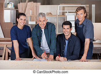 Confident Carpenters Working In Workshop