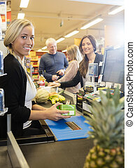 Confident Cashier Holding Juice Packet At Checkout Counter