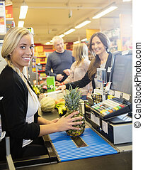 Confident Cashier Holding Pineapple At Checkout Counter In Super