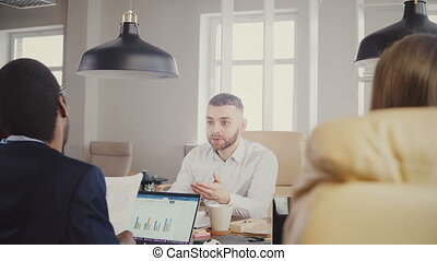 Confident Caucasian young businessman leading multiethnic office meeting. Diverse business people discuss contract 4K.