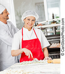Confident Chef Cutting Ravioli Pasta With Colleague In Backgroun