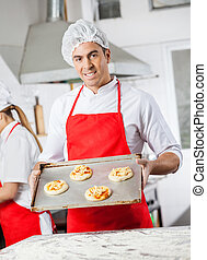 Confident Chef Holding Pizzas On Tray In Kitchen