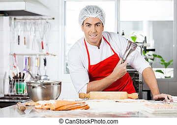 Confident Chef Holding Tongs While Preparing Ravioli Pasta In Ki
