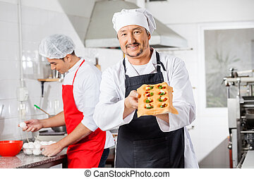 Confident Chef Holding Tray With Stuffed Pasta Sheet In Kitchen