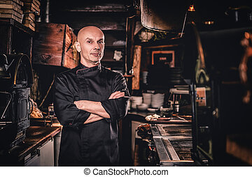 Confident chef posing with his arms crossed and looking at a camera in restaurant kitchen.