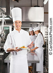 Confident Chef Presenting Dish In Commercial Kitchen