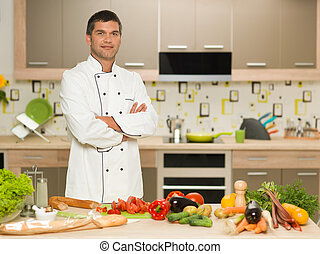 confident chef standing in kitchen - portrait of young...