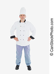 Full length of confident chef standing with arms akimbo against white background
