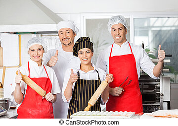 Confident Chef Team Gesturing Thumbsup In Kitchen