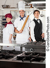 Confident Chefs And Waiter In Kitchen