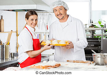 Confident Chefs Holding Pasta Tray In Kitchen