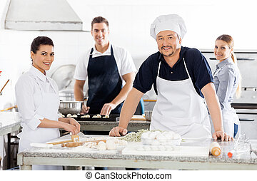 Confident Chefs Preparing Pasta At Kitchen