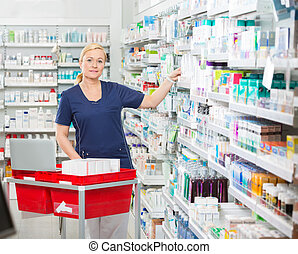 Confident Chemist Arranging Medicines In Shelves At Pharmacy