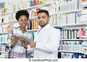 Confident Chemist Holding Digital Tablet By Customer