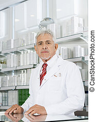 Confident Chemist Standing At Counter In Pharmacy