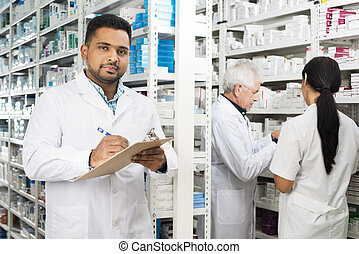 Confident Chemist Writing On Clipboard While Colleagues Standing