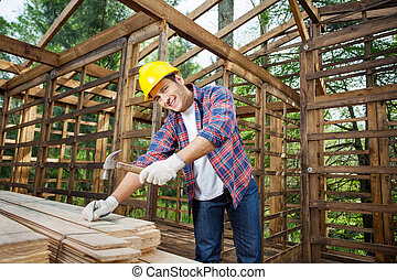 Confident Construction Worker Hammering Nail On Wooden Plank