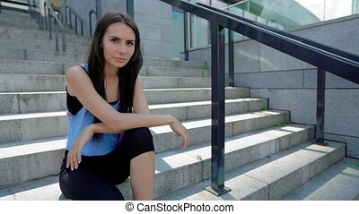 Confident coquettish female athlete sitting on the stairs taking a break from running, looking and smiling at camera