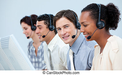 Confident customer service representatives with headset on in a call center