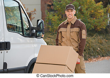 Confident Delivery Man Pushing Parcels On Handtruck -...