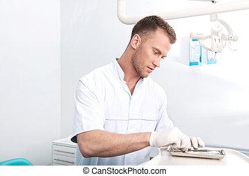 Confident dentist. Confident young dentist preparing dental equipment