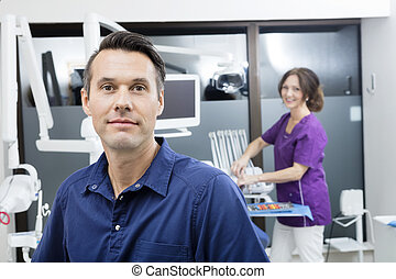 Confident Dentist With Female Assistant Smiling At Clinic