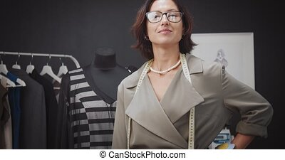 Portrait of confident woman in eyeglasses standing near mannequin with trendy dress and looking at camera. Concept of tailoring and inspiration.