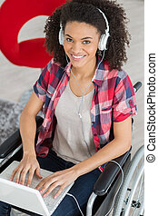 confident disabled woman using laptop at desk in creative office