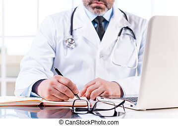 Confident doctor at work. Close-up of mature doctor writing something in note pad while sitting at his working place