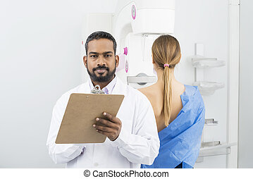 Confident Doctor Holding Clipboard While Patient Undergoing Mamm