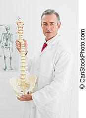 Confident doctor holding skeleton model in office - Portrait...