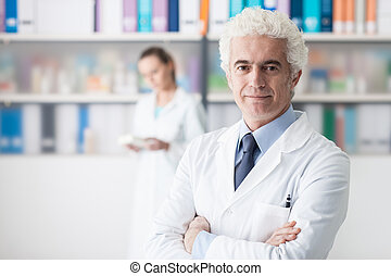 Confident doctor posing in his office