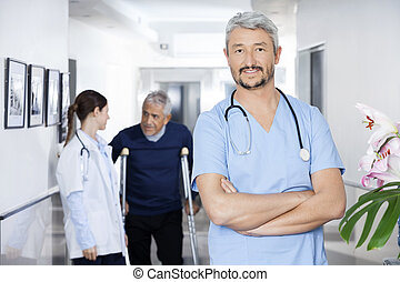 Confident Doctor Standing With Colleague And Senior Patient In B