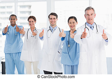Confident doctors gesturing thumbs up at hospital