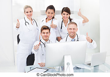 Confident Doctors Gesturing Thumbs Up