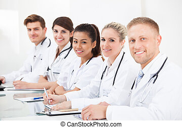 Confident Doctors Sitting In A Row