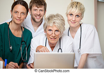 Confident Doctors With Laptop In Hospital - Confident male...