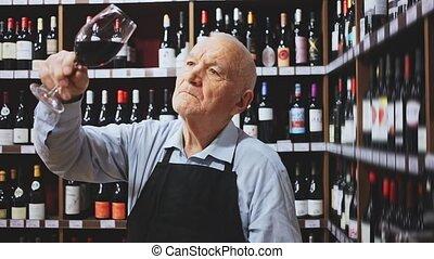 Portrait of senior man professional sommelier tasting red wines in wine store