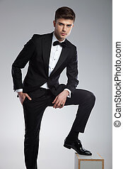 confident elegant man resting his foot on a wooden box