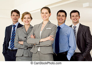Portrait of successful businesswoman smiling at camera with several employees standing next to her