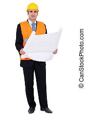 Confident entrepreneur looking at blueprints