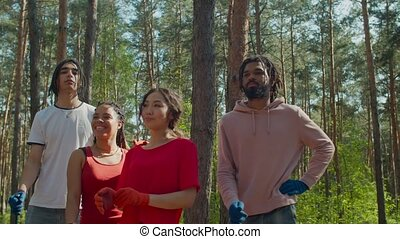 Confident determined team of multiracial diverse environmental activists in protective gloves with garden tools preparing for cleaning forest garbage. Environment protection and preserving nature.