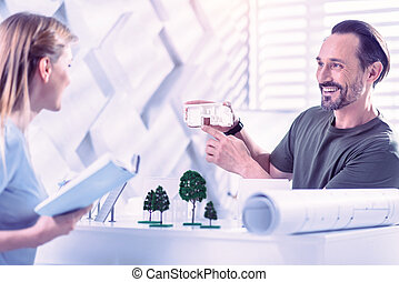 Confident estate agent smiling and showing beautiful house miniature